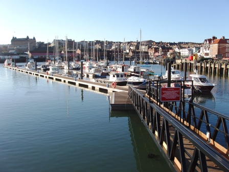 Image shows the boats within the pretty harbour of Scarborough.