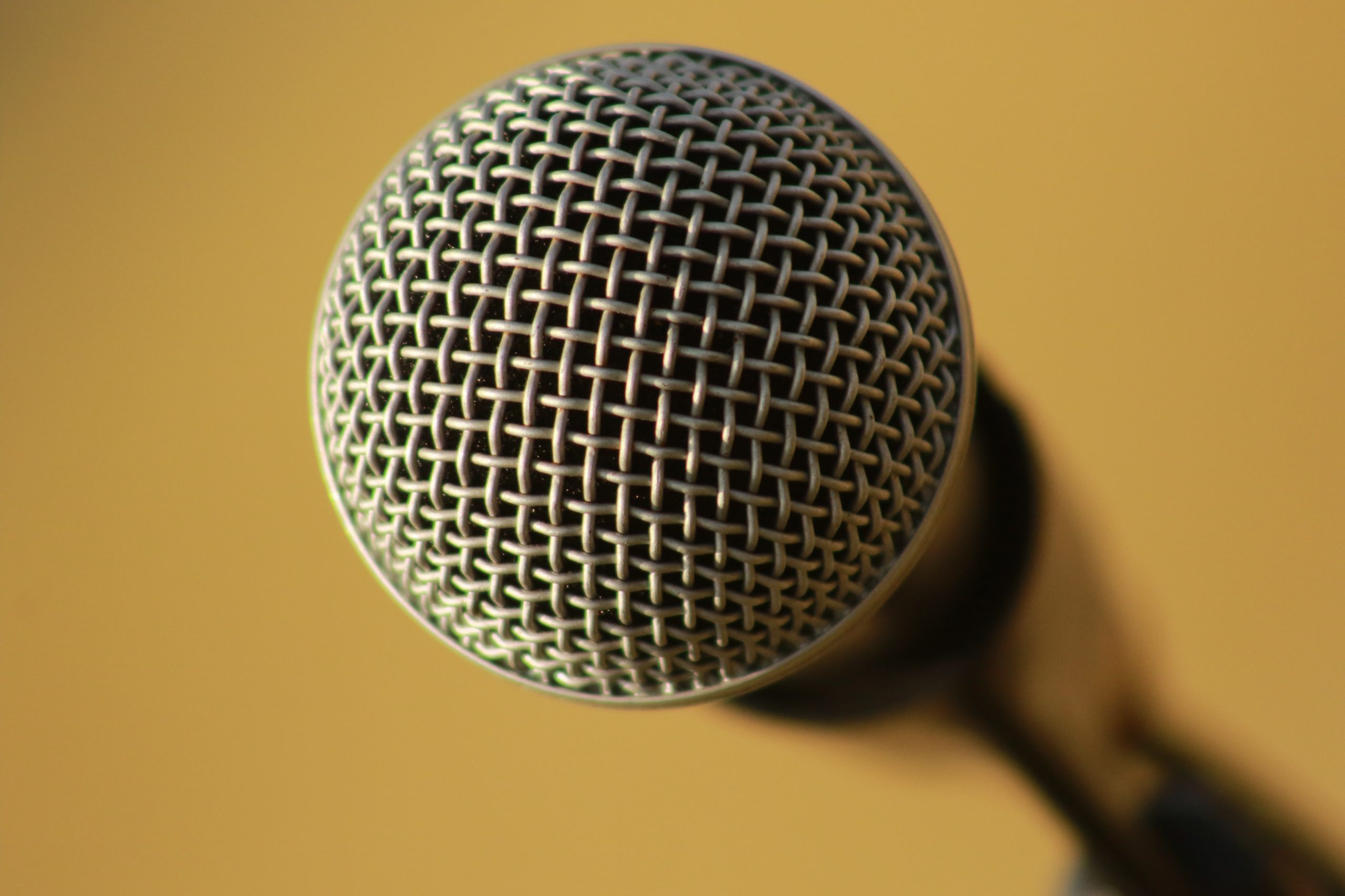 Image shows close up shot of the top of a microphone, against a mustard yellow background.