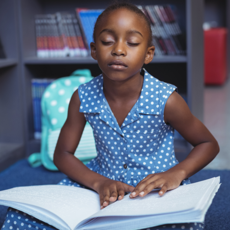 Image shows a young girl, reading a braille book, wearing a blue dress with white polka dots.