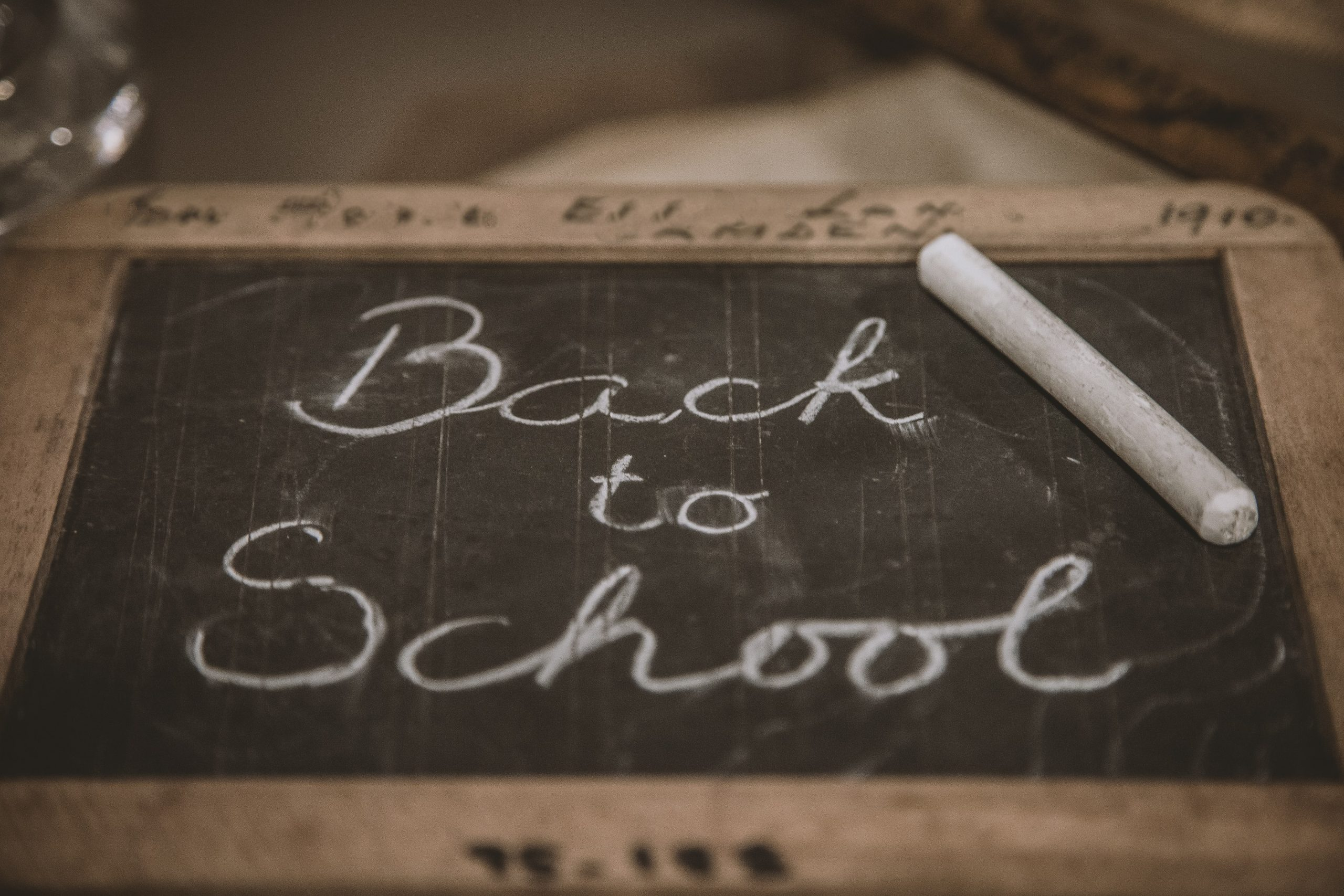 Old-fashioned mini-chalkboard has 'Back to School' written on it in white chalk with the chalk stick resting on top.