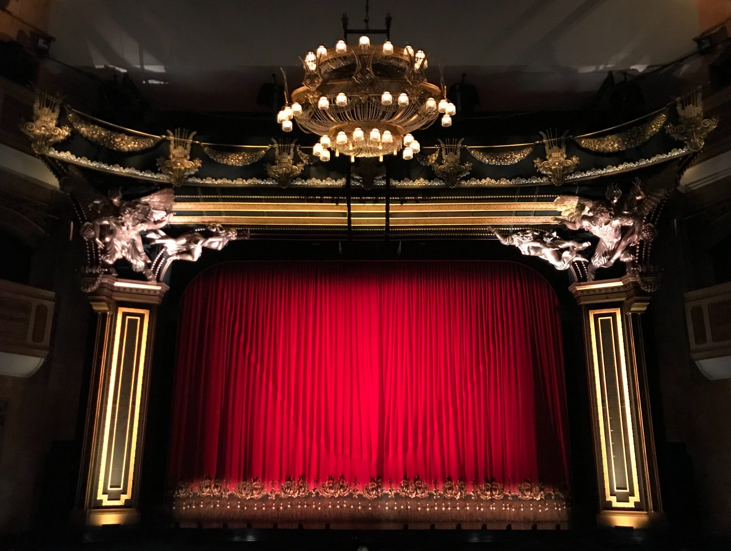 Image shows the red curtains of a theatre stage, with ornate surround and grand chandelier.