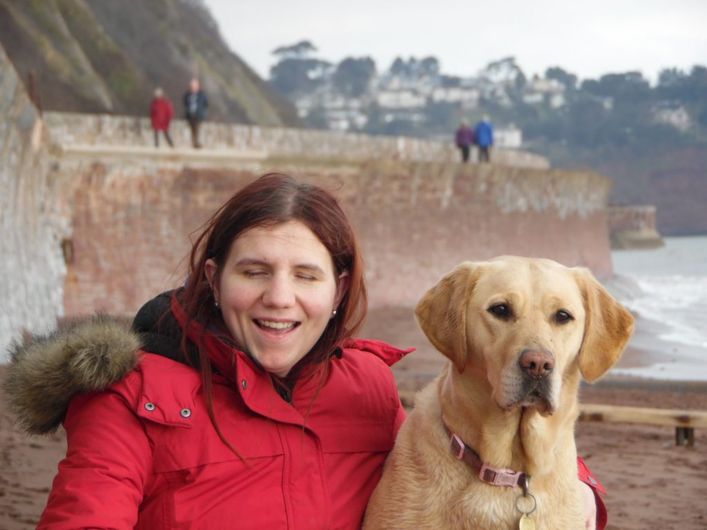 Image shows Andrea on the left hand-side, sat on a beach wearing a vibrant red jacket with fur-lined hood, with an arm around her gorgeous golden labrador guide dog. Sea and cliffs just in the background.