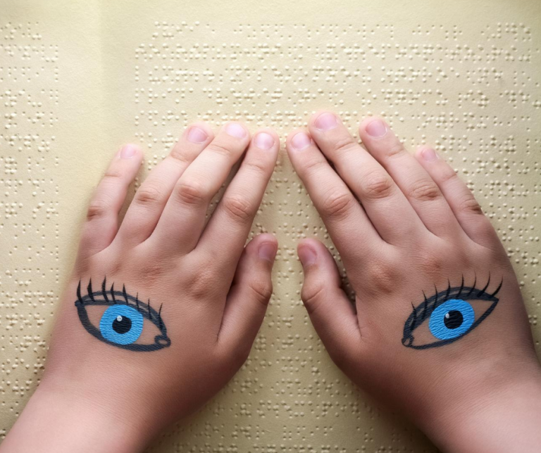 Image shows a pair of child's hands with a blue eye drawn on the top of each hand, as the fingers scroll across a cream-coloured page of braille.