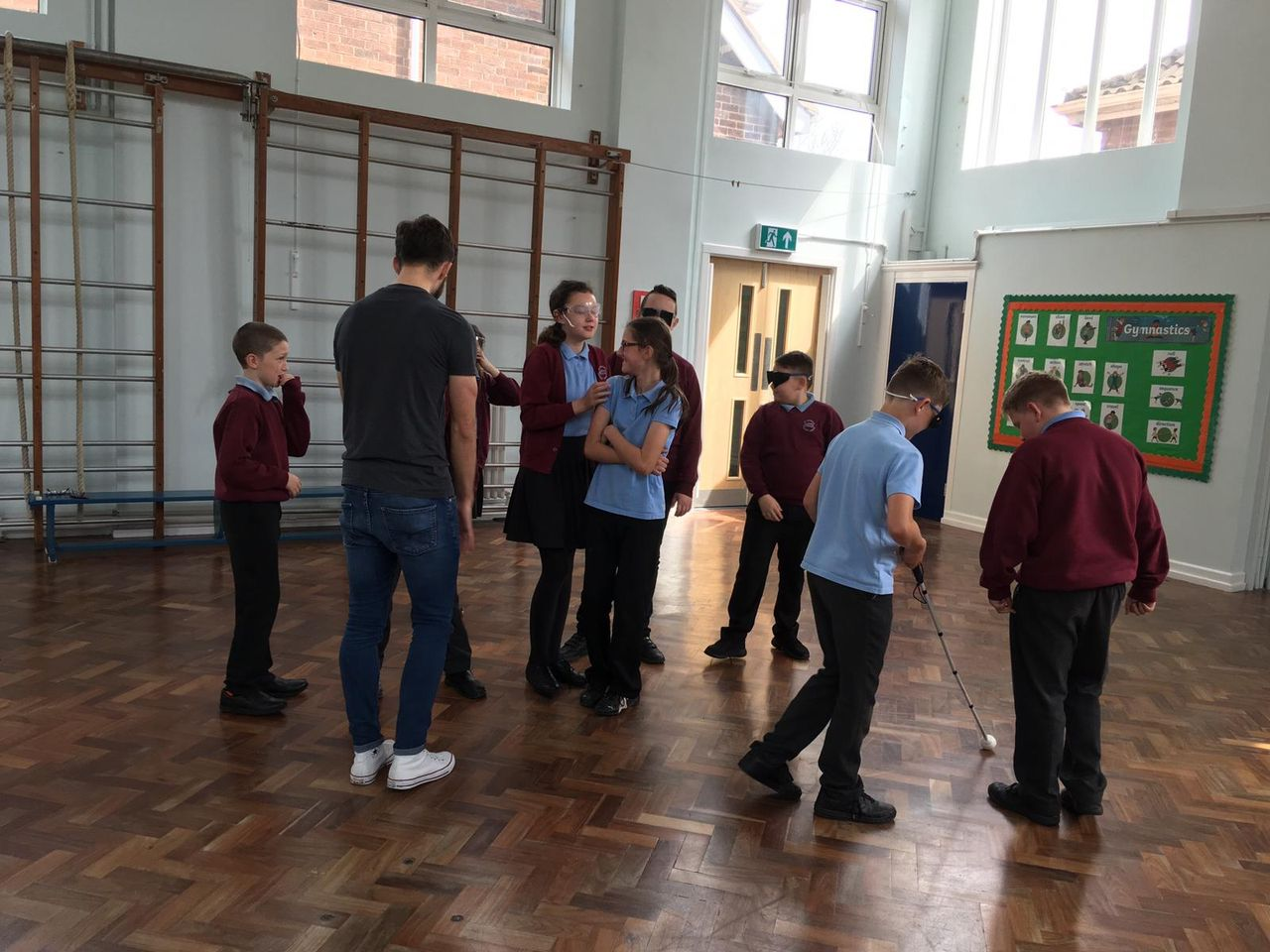 Chris with a group of young school pupils in a school sports hall.