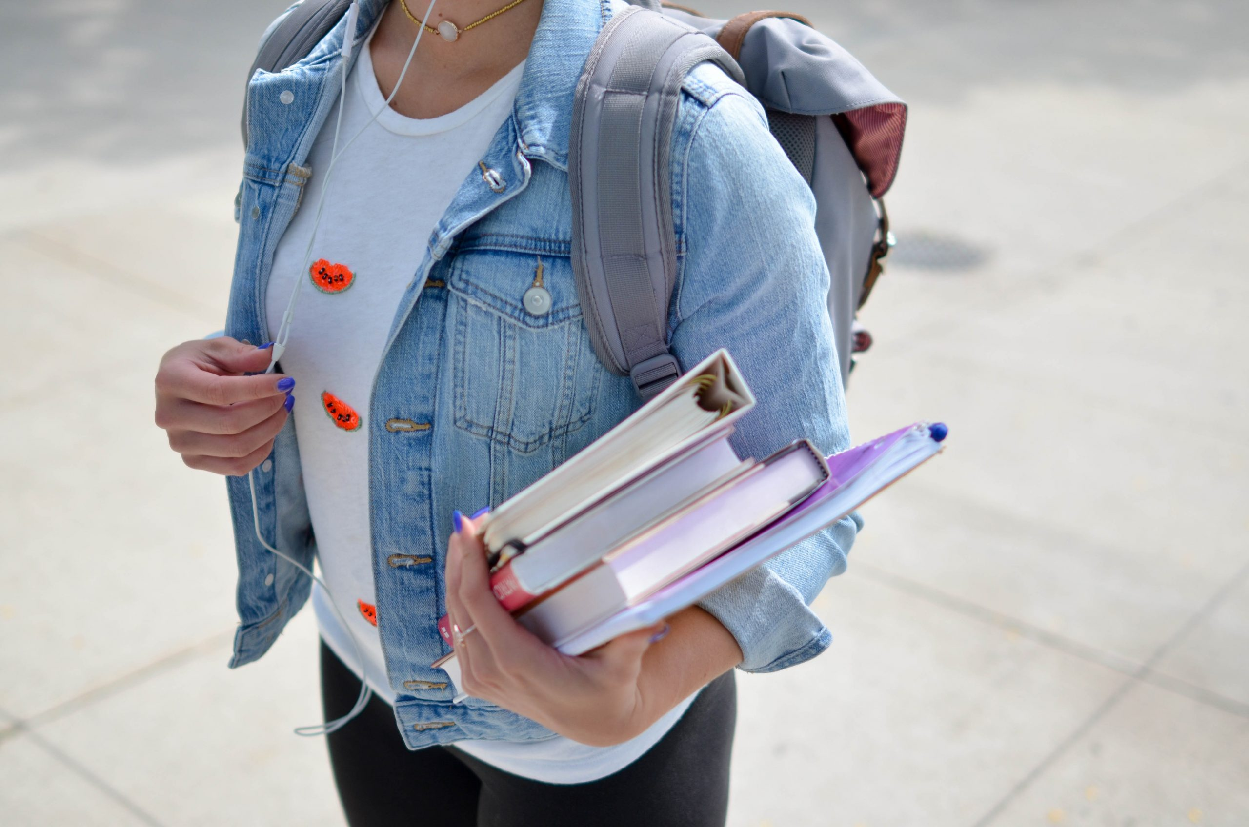 Image shows a female student (face not in shot), wearing a denim jacket, white t-shirt and grey rucksack, carry 4 books and wearing headphones.