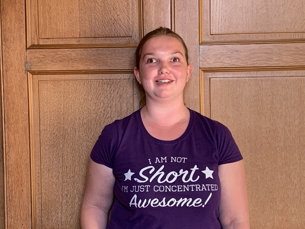 Image shows Natalie wearing a purple t-shirt with white writing on that says: 'I am not short, just concentrated. Awesome!'