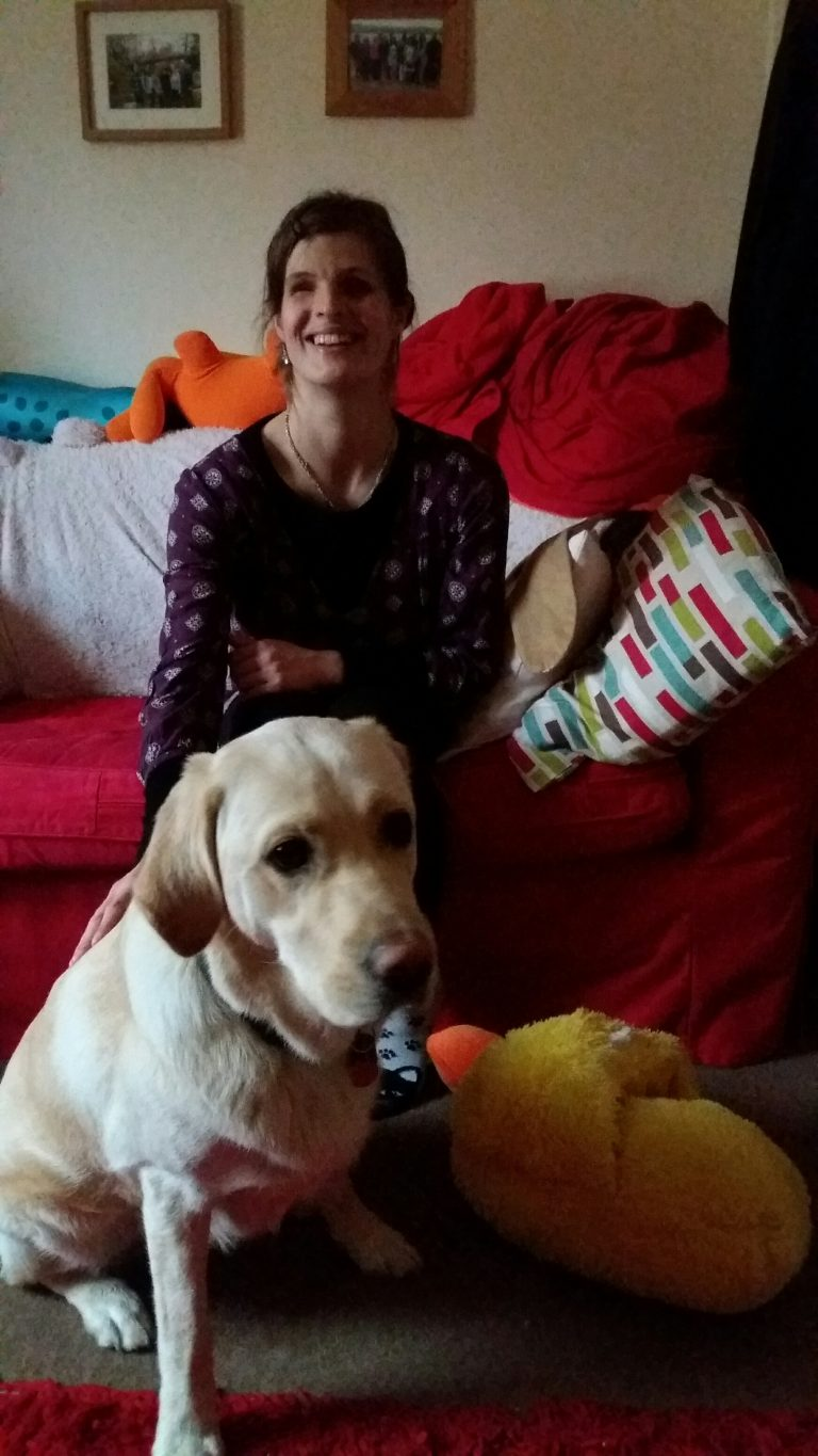 Image shows a smiling Megan sat in front of a red sofa. Lovely Layla, her guide dog, sits in front of her.