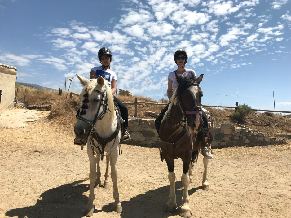 Zarie sits on a beautiful white horse with tassled bridle. Zarie wears a riding hat and white t-shirt. Mum is on the right on brown and cream horse. Both looking at the camera, with blue sky overhead and a dusty floor underfoot.