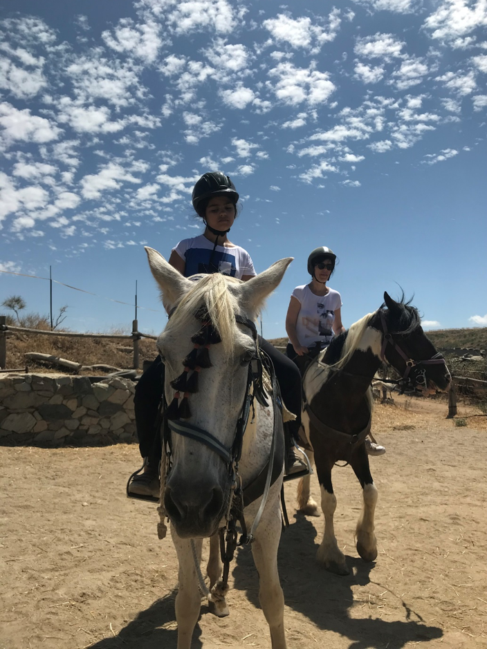 Image shows Zarie on a beautiful white horse with tassles on its bridle. Mum is on a white and brown horse in the background, with blissful blue sky overhead.