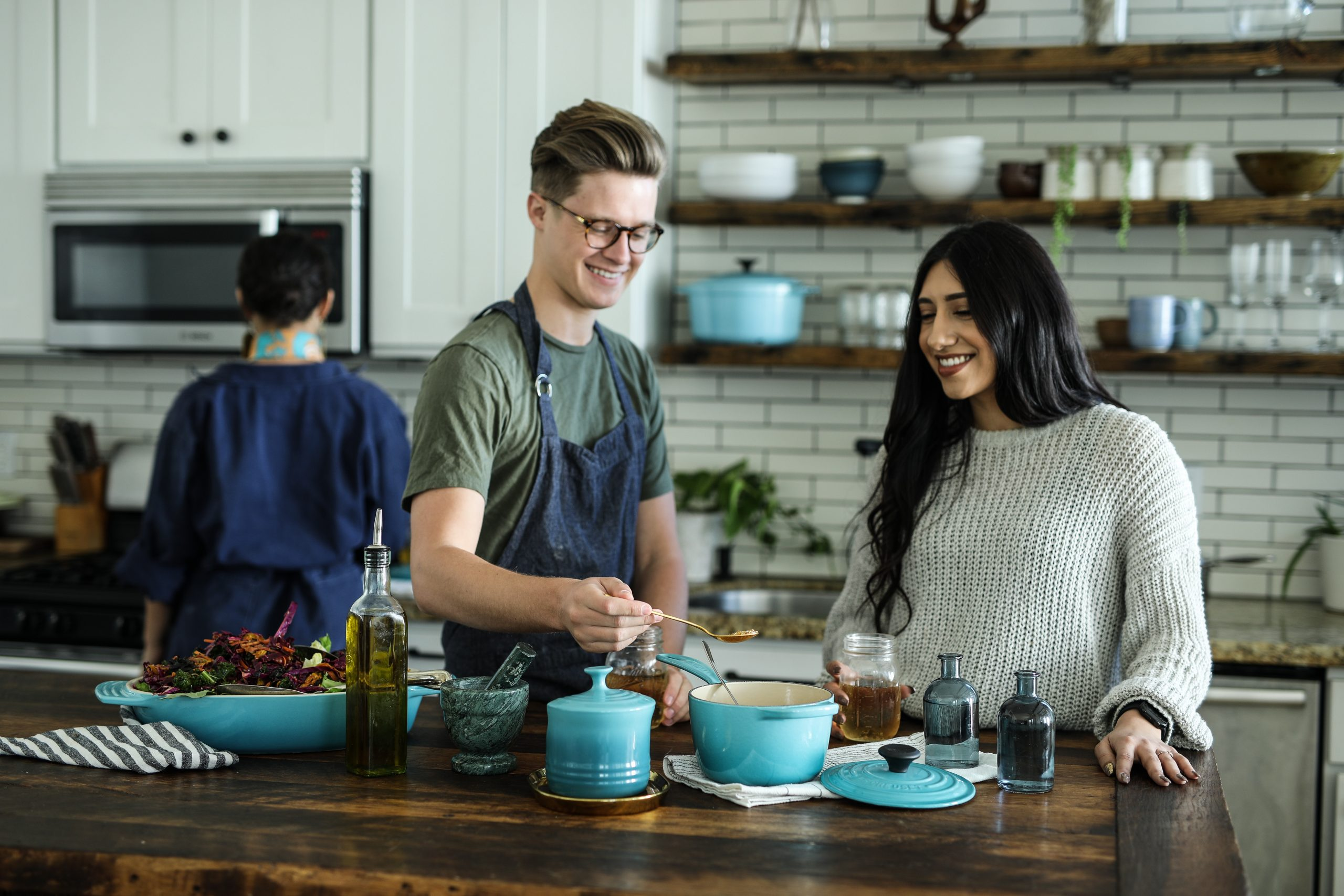 Image shows two people, one male one female, stood in a kitchen at the island, surrounded by blue Le Creuset-style kitchen pots and food. One person just visible in the background stood at the oven.