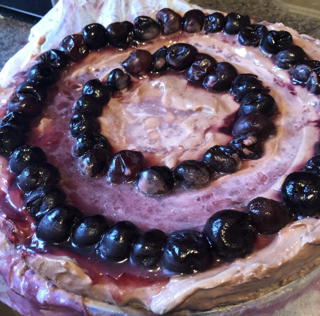 Image shows a close-up birds-eye view of the cheesecake. The top shows a delicious purpley-creamy mixture with two circles of blueberries. The biscuit base is just visible.