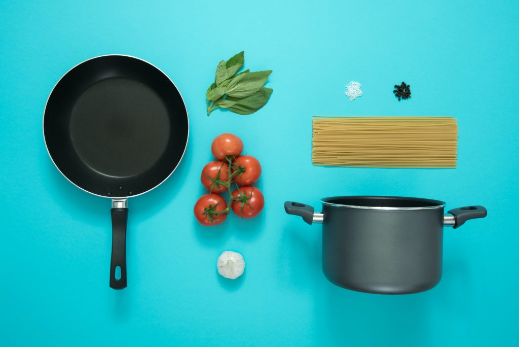 Image shows a flat lay of a fying pan, saucepan, basil leaves, red tomatoes, white garlic bulb, pile of salt, black peppercorns and dried spaghetti.