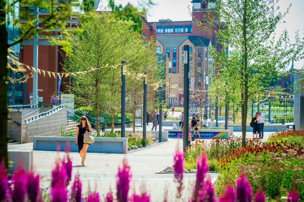 A photo of the fantastic green space that runs through the heart of the campus from the city centre right down to the River Soar. Photo shows colourful flower beds, trees, buildings, bunting and people walking along the promenade.