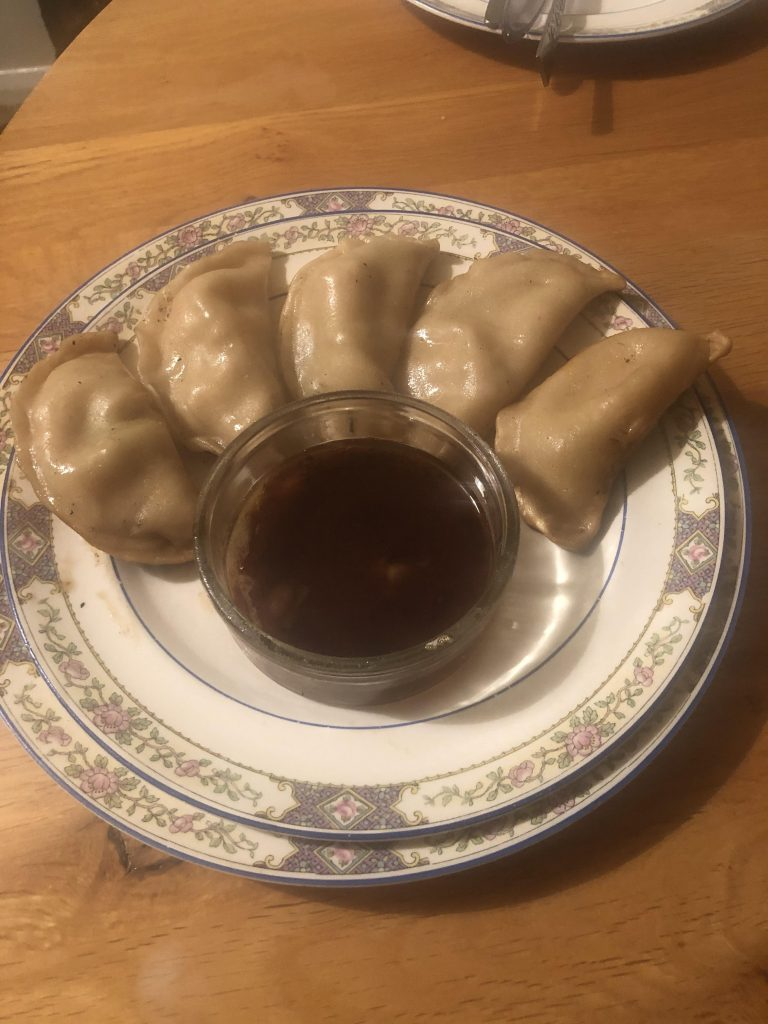 A photo of George's five gyoza arranged around a glass bowl of dipping sauce, all on two stacked white plates with decorative borders.