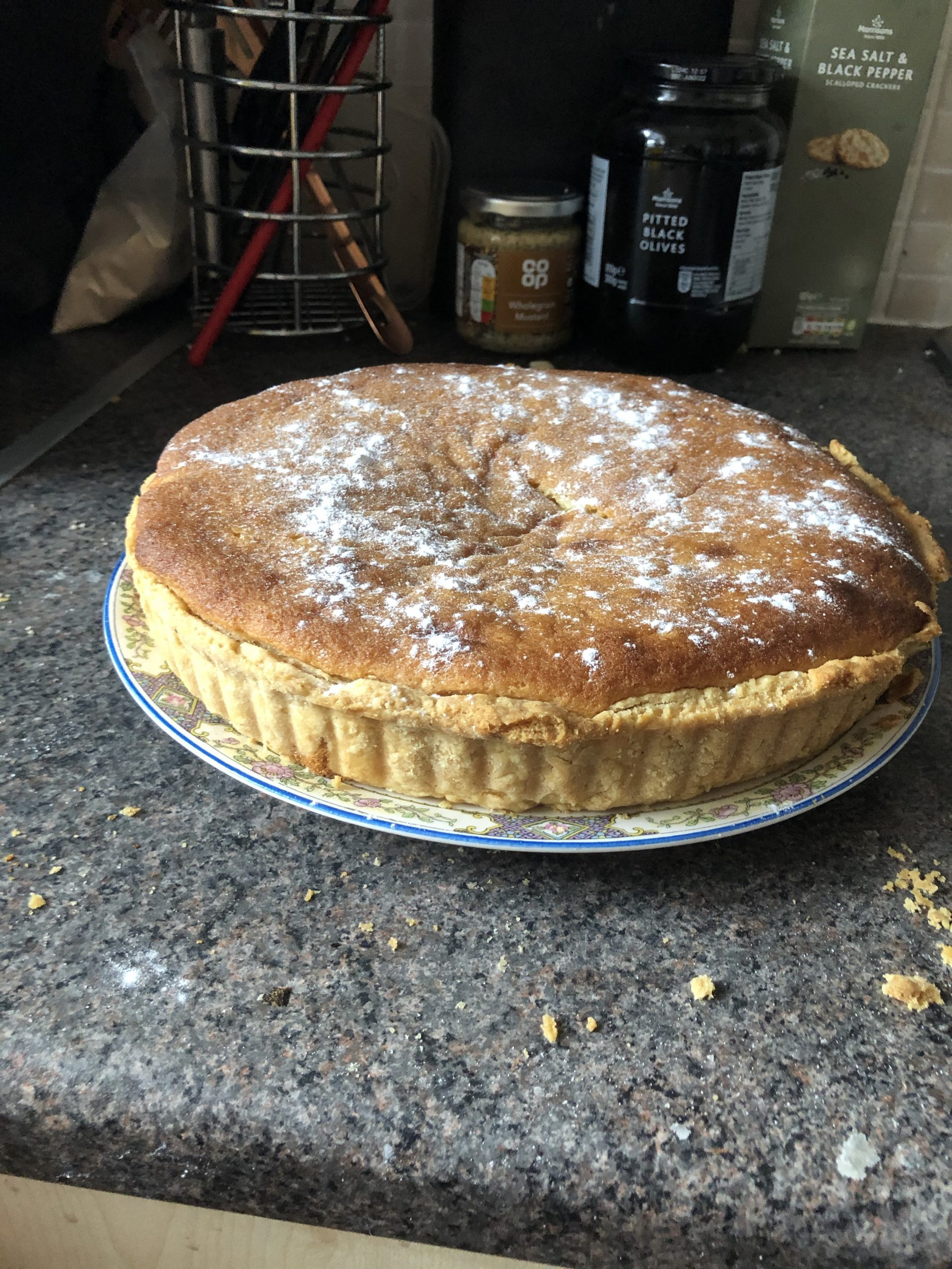 A photo of the delicious Bakewell tart in its entierty, on a white plate sat on a grey worktop.
