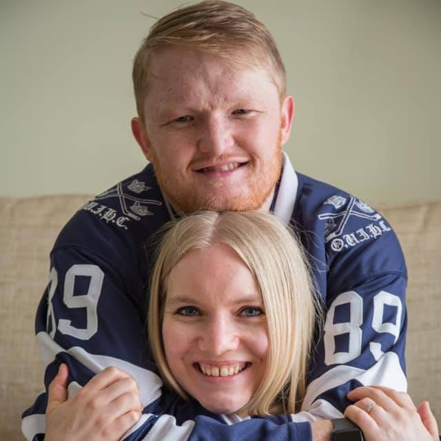 Photograph of Nathan with his fiancée, Ginny. Nathan stands behind a sitting Ginny, with his chin resting on the top of her head. His arms are around her and Ginny holds on to his forearms. Both are beaming at the camera.