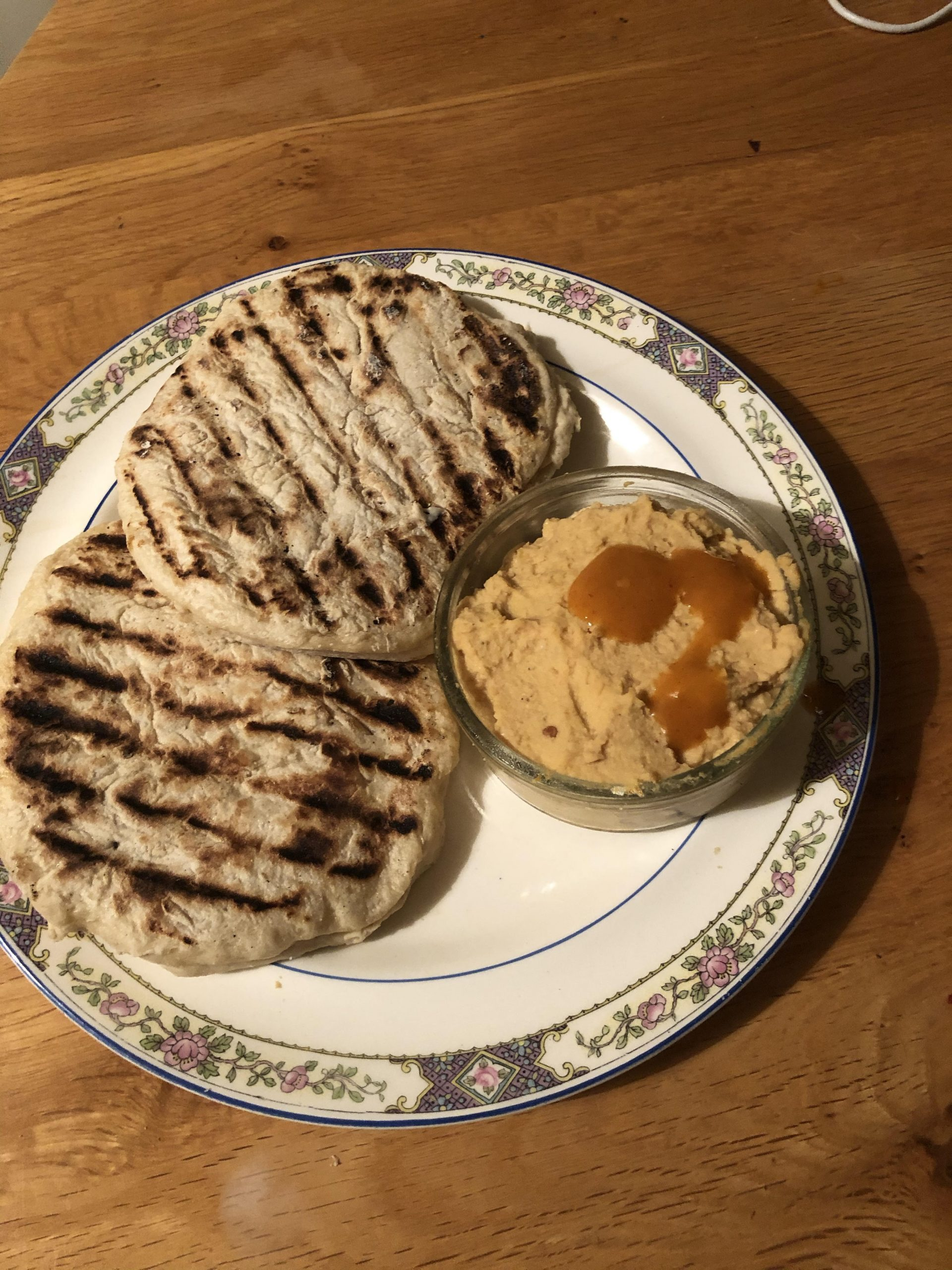 Image shows two round flatbreads with charred griddle lines going through each, next to a bowl of beige hummus with orange piri piri sauce on top, all served on a white plate with decorative border on top of a brown wooden table.