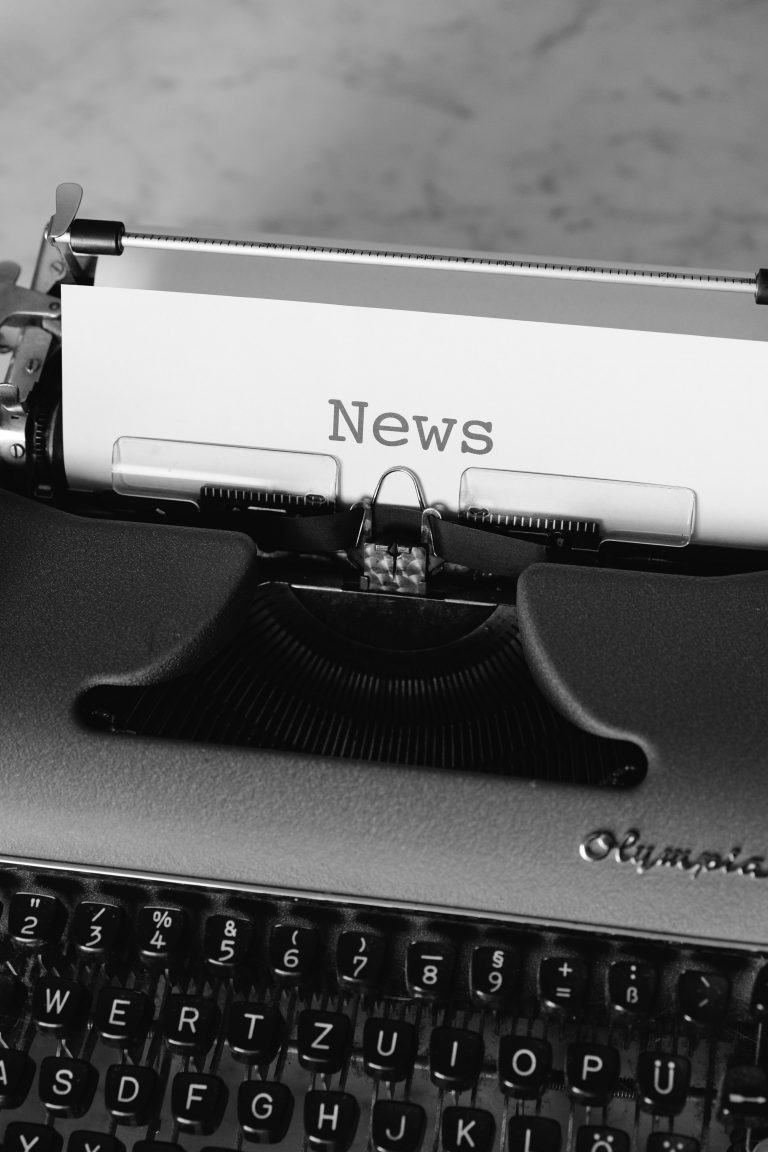 The image is a black and white photo of an old-fashioned 'Olympia' typewriter with a piece of white paper threaded through and the word 'News' typed at the top.