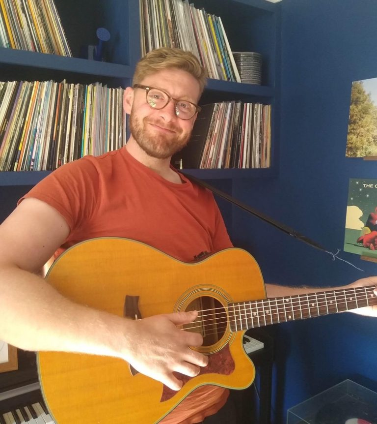 Rupert stood up with an acoustic guitar on smiling at camera in orange t-shirt and glasses. Behind him are hundreds of vinyl records in shelves!
