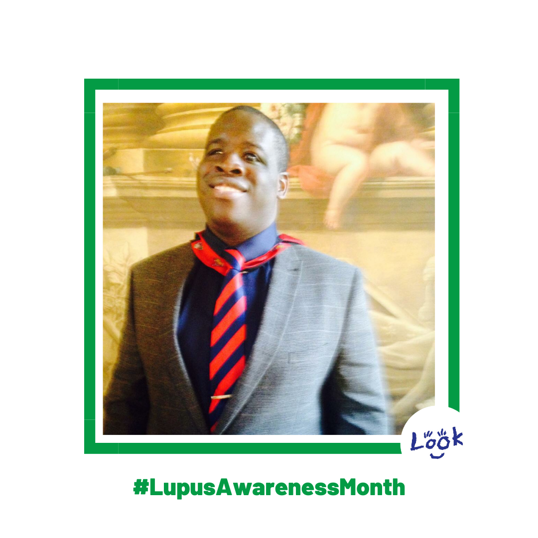 Photo of Sam, wearing a grey blazer, navy shirt and red and navy striped tie, stood in front of a fresco. Photo is set within green frame, on a white background with #LupusAwarenessMonth written in green. LOOK logo in bottom right corner.