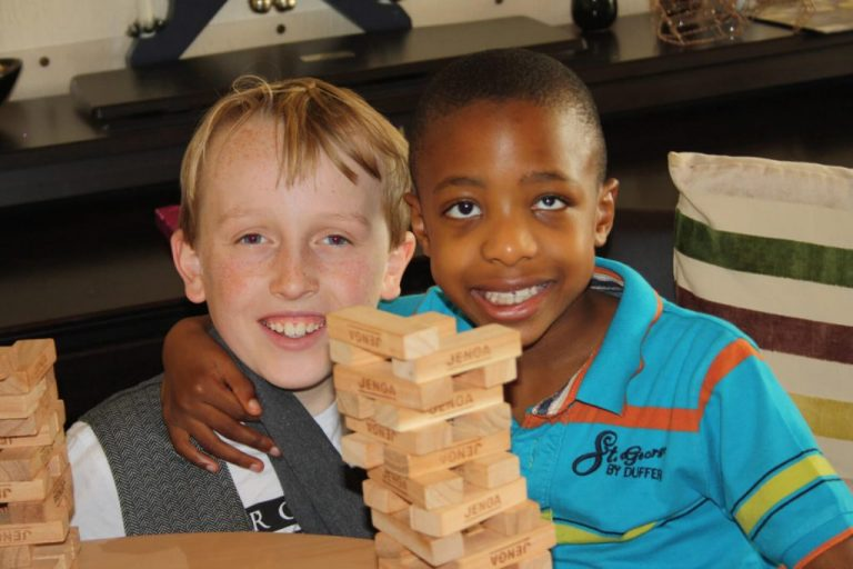 Two young boys with arms around each other and smiling, playing Jenga.