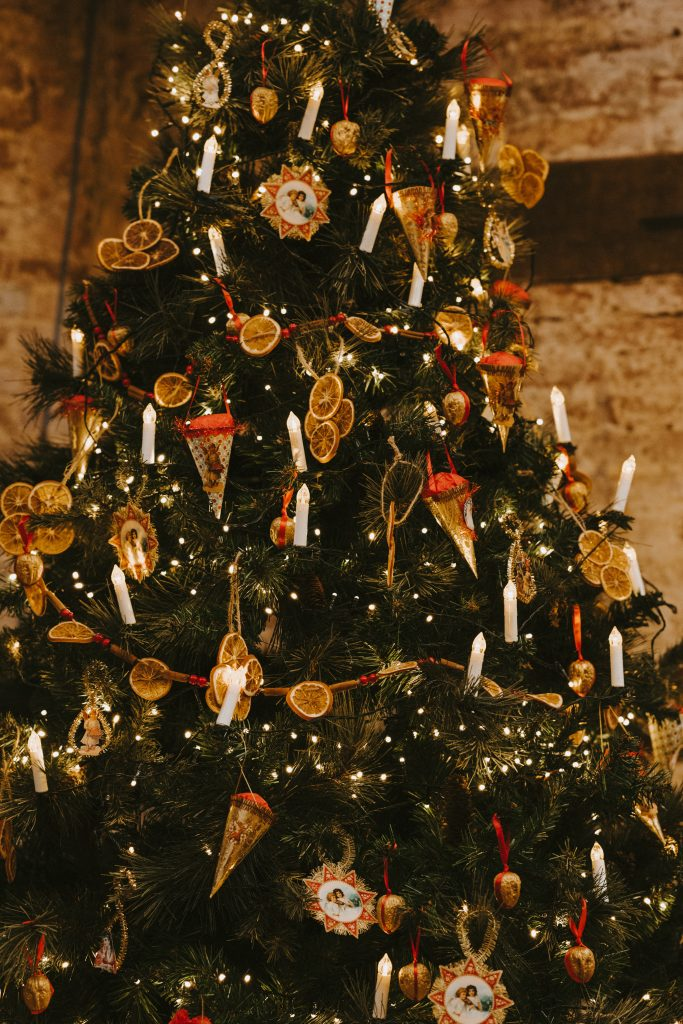 Photo of a beautifully decorated Christmas tree, featuring white candle-style lights, dried oranges, red ribbons and gold tinsel.