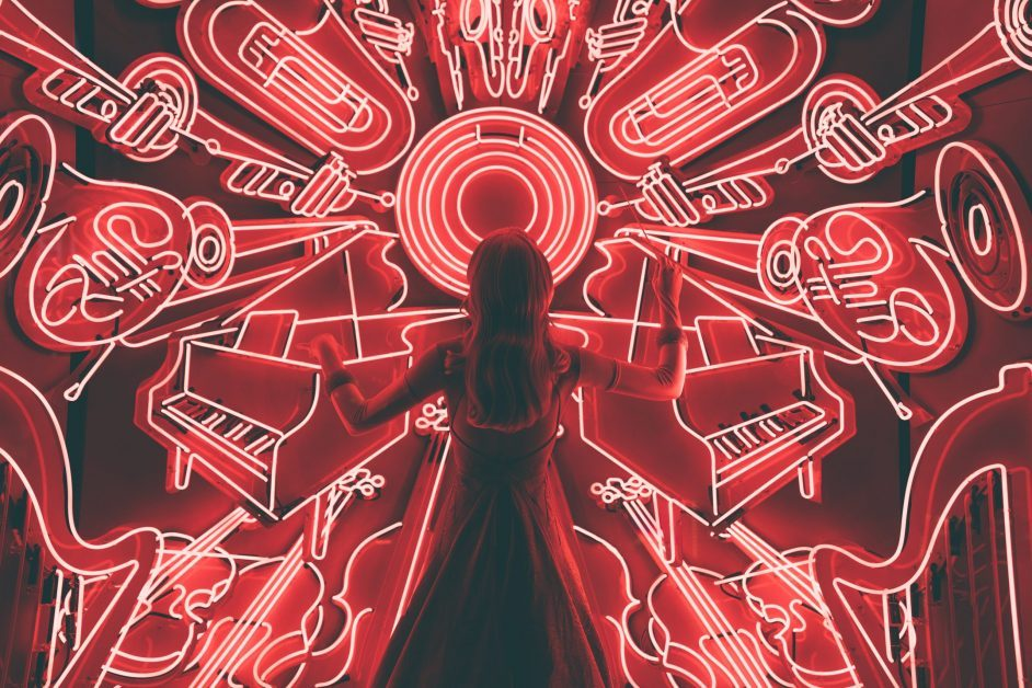 Image, mounted on a red background, shows the back of a girl wearing a dress and holding a conductors baton. She stands in front of a screen with neon lights in the shape of musical instruments; french horns, pianos, trumpets, violins, cellos and harps. The whole image has a red filter over it, with the instruments outlined in white.