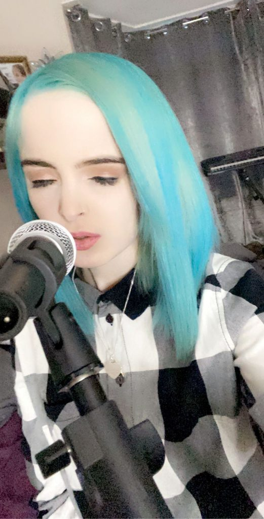 Photo of blue-haired Paige wearing a black and white lumberjack style shirt, singing into a microphone.