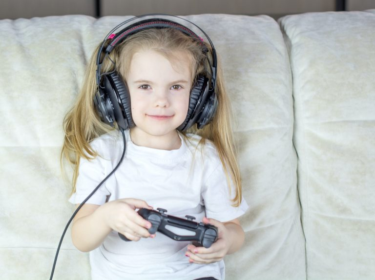 Photo of a young girl with a white sofa cushion behind her, wearing large headphones and holding a gaming controller.