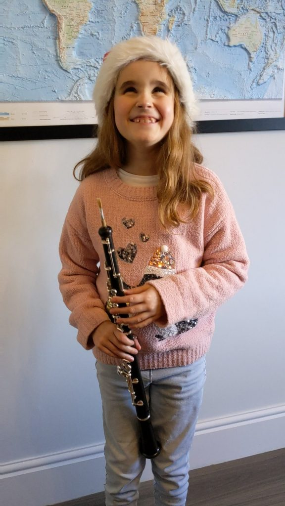 Photo of Ellie wearing a Santa's hat and holding her oboe.