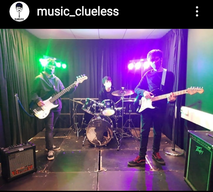 Photo of 3 band members = two guitarists and one drummer with their instruments on stage.