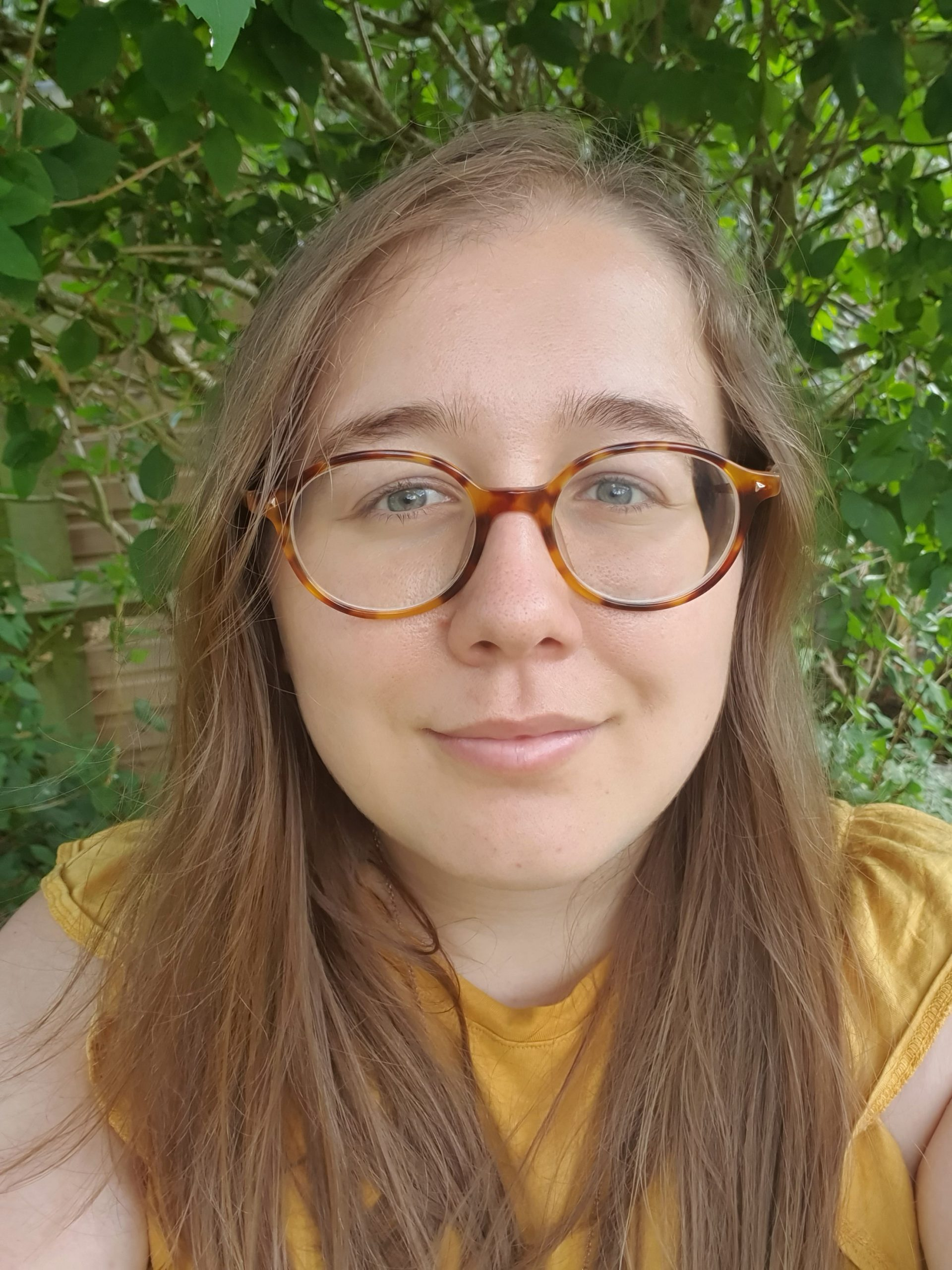 Head and shoulders photo of Brigitta, wearing a yellow top and smiling at the camera.