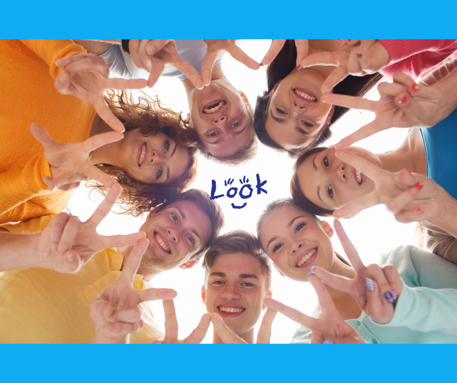 A worms-eye-view of a group of young people looking down at the camera and smiling. They stand in a circle, heads touching and holding the 'V/Peace' sign with hands touching.