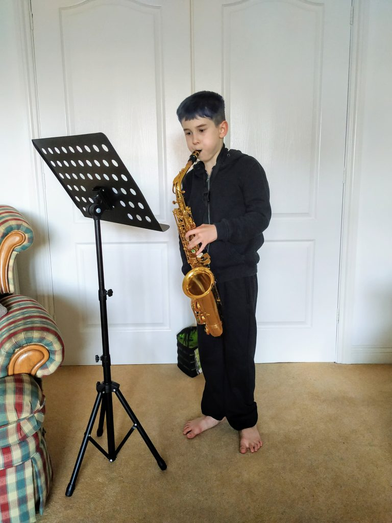 Photo of youngster Jack, playing his Saxophone, stood in front of his music stand.