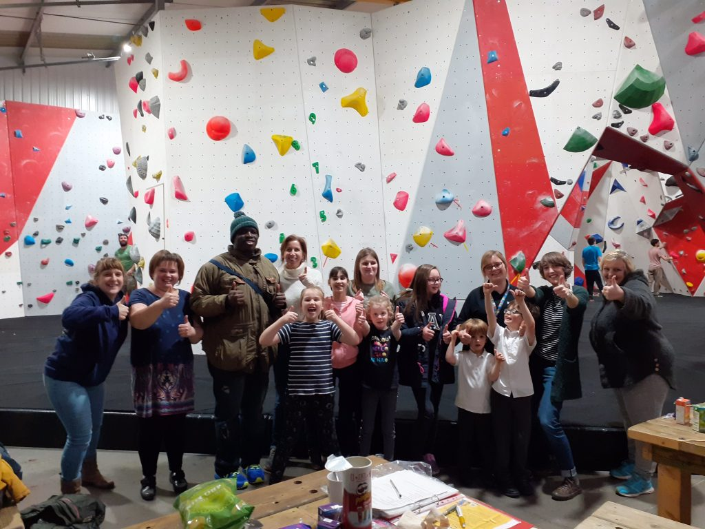 Photo of members of the LOOK team, Mentors, Mentees and family members all stood in front of a climbing wall giving the thumbs up to the camera!