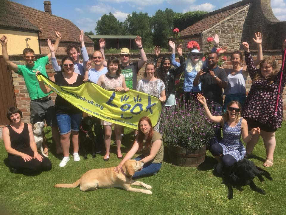 Photo of LOOK Mentors, members of the LOOK team, friends of LOOK and family members sat and stood on a lawn with hands in the air, smiling and waving a yellow 'LOOK' banner.