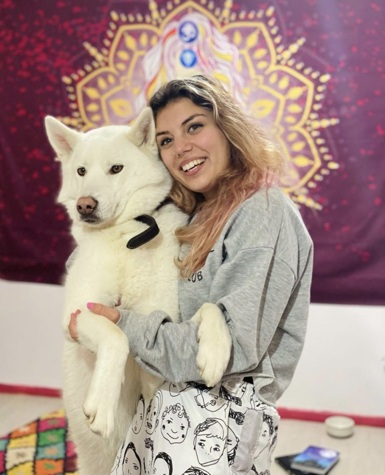 Photo of Naz holding a beautiful pure white huskie dog which is standing on its back legs and is almost the same height as her!