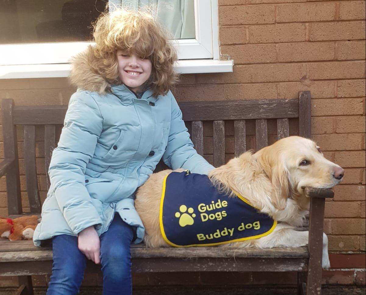 Photo of Chloe sat on a bench with her buddy guide dog, Sapphire.