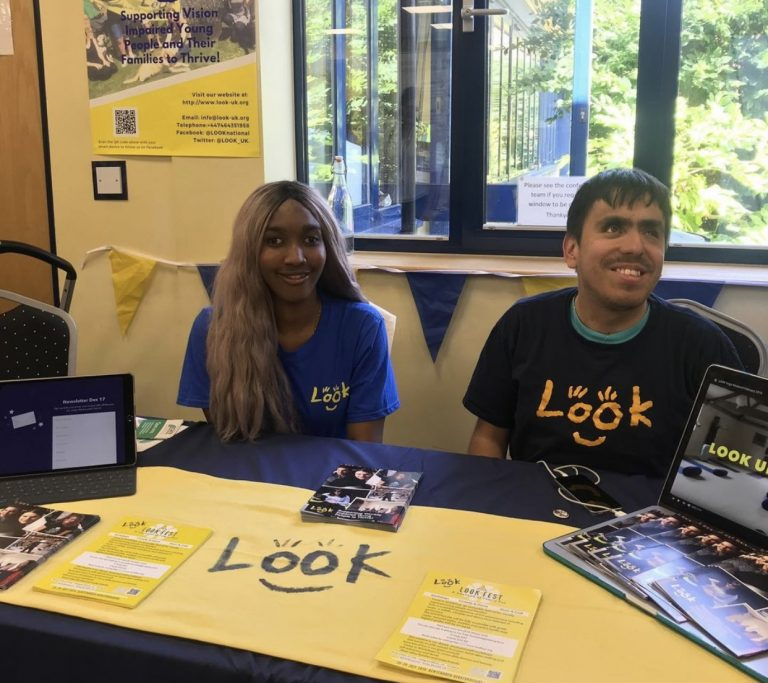 Photo of LOOK mentors Abi and Kevin sat at a table wearing LOOK t-shirts at an event.