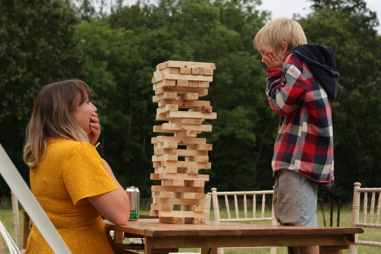 Woman and young boy sit either side of a very tall Jenga tower!