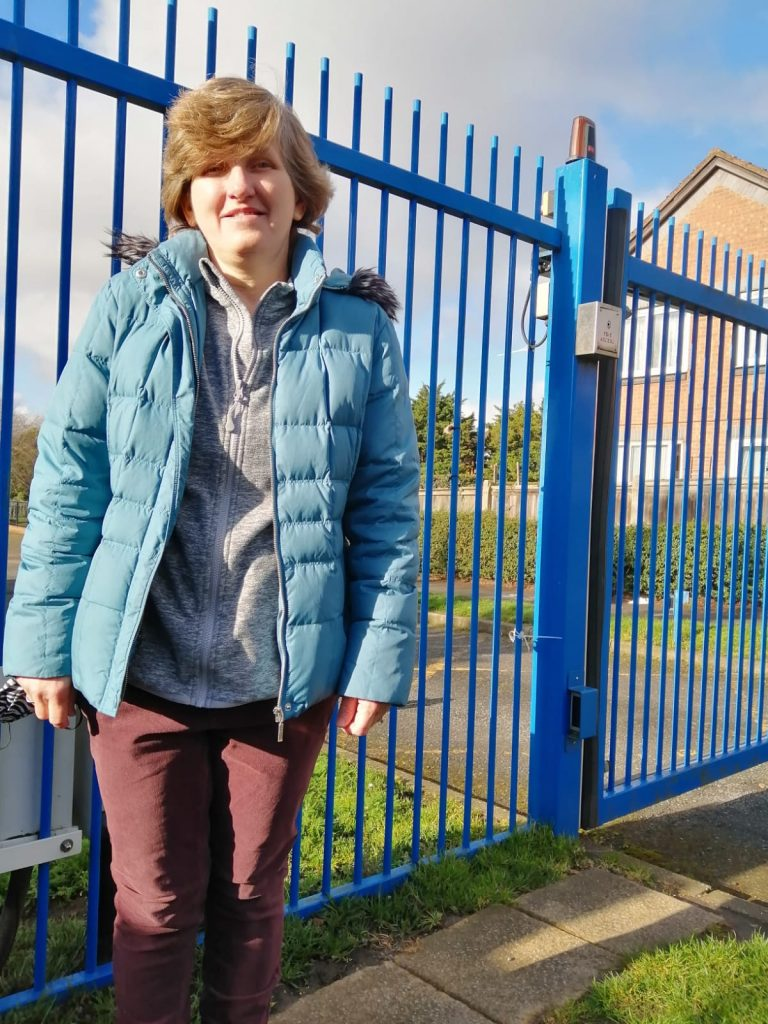 Photo of Julie, stood in front of blue railings.