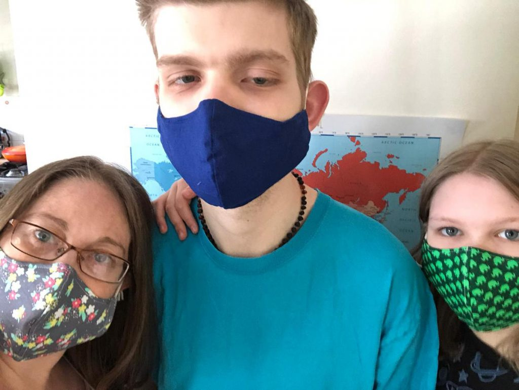Photo of mum Sarah with son Lucas and daughter, all wearing face masks with arms around each other.