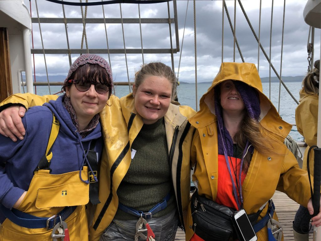 Photo shows three women stood in a line on a boat with arms around each other wearing yellow waterproofs.