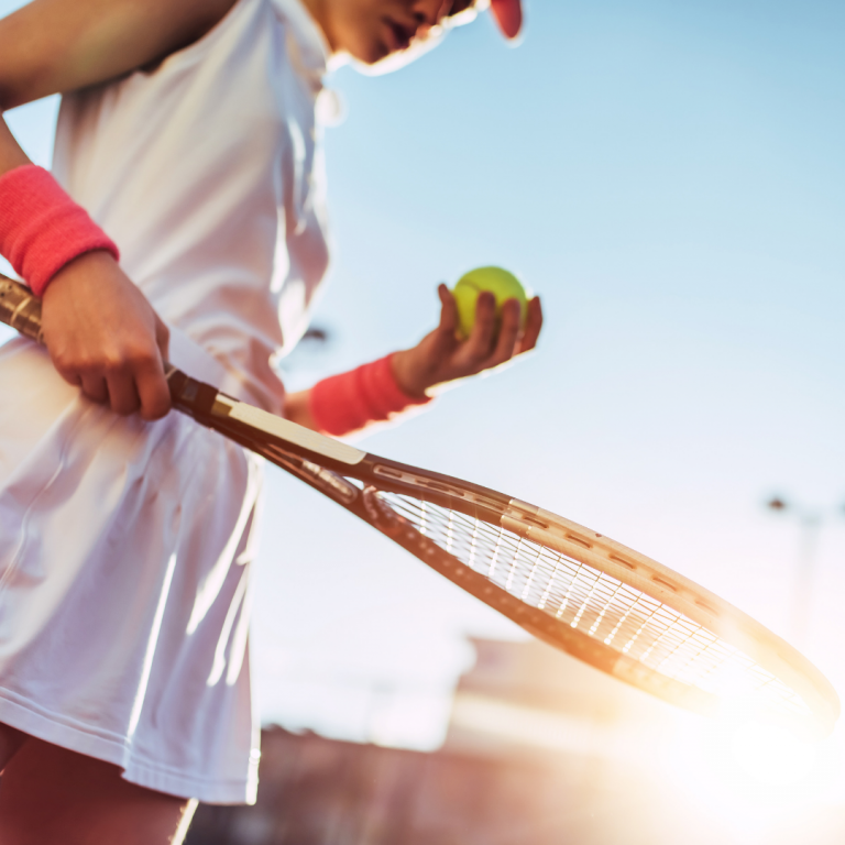 Photo of a girl holding a tennis racket and tennis ball.