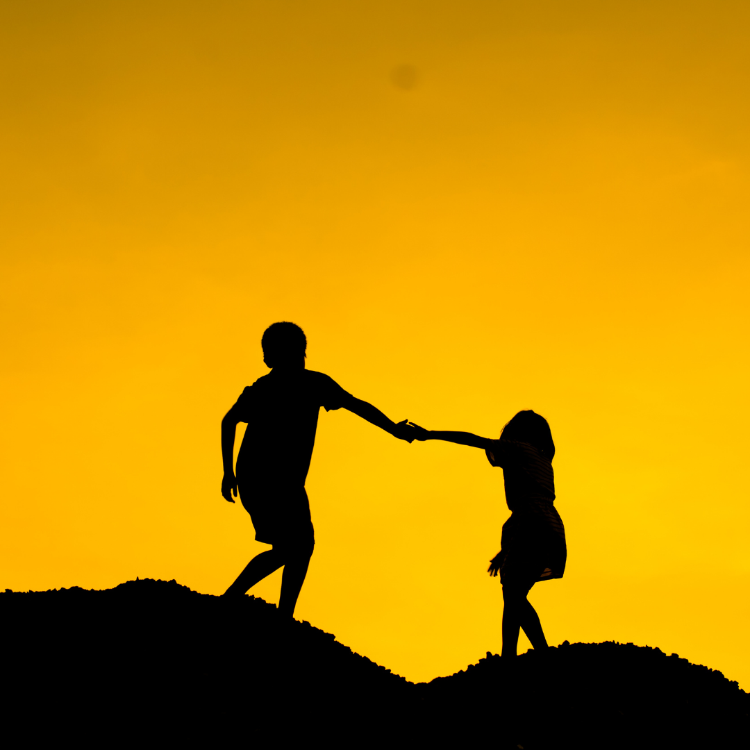 Image shows the silhouettes of two people helping each other up a hill. Set against a yellowy-orange skyline.