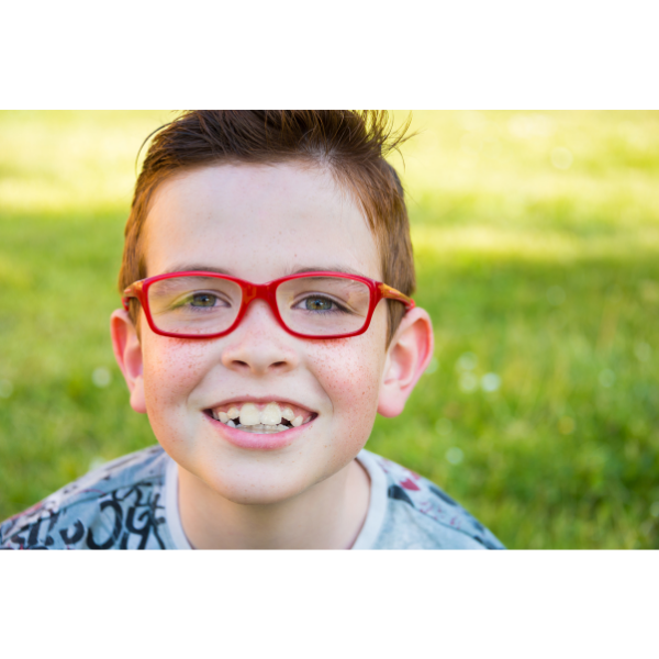 Photo of a young boy wearing red-rimmed glasses, smiling at the camera with a grass lawn in the background.