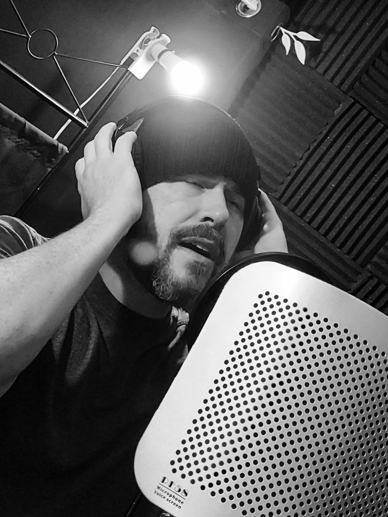 Black and white photo of Dan wearing a beanie singing into a microphone.