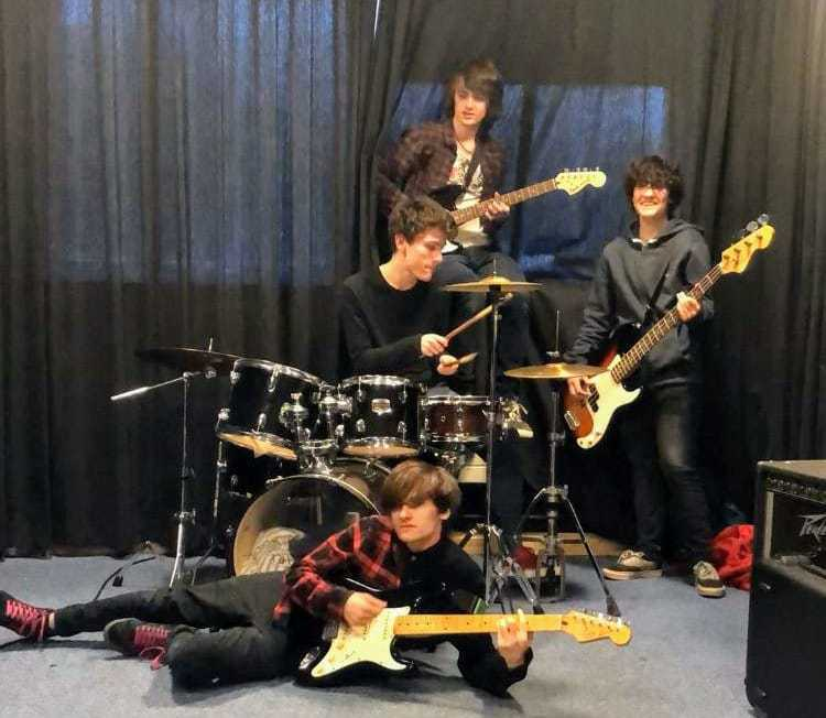 Photo of the band, Clueless, featuring three guitarists (one lay on floor) and a drummer.