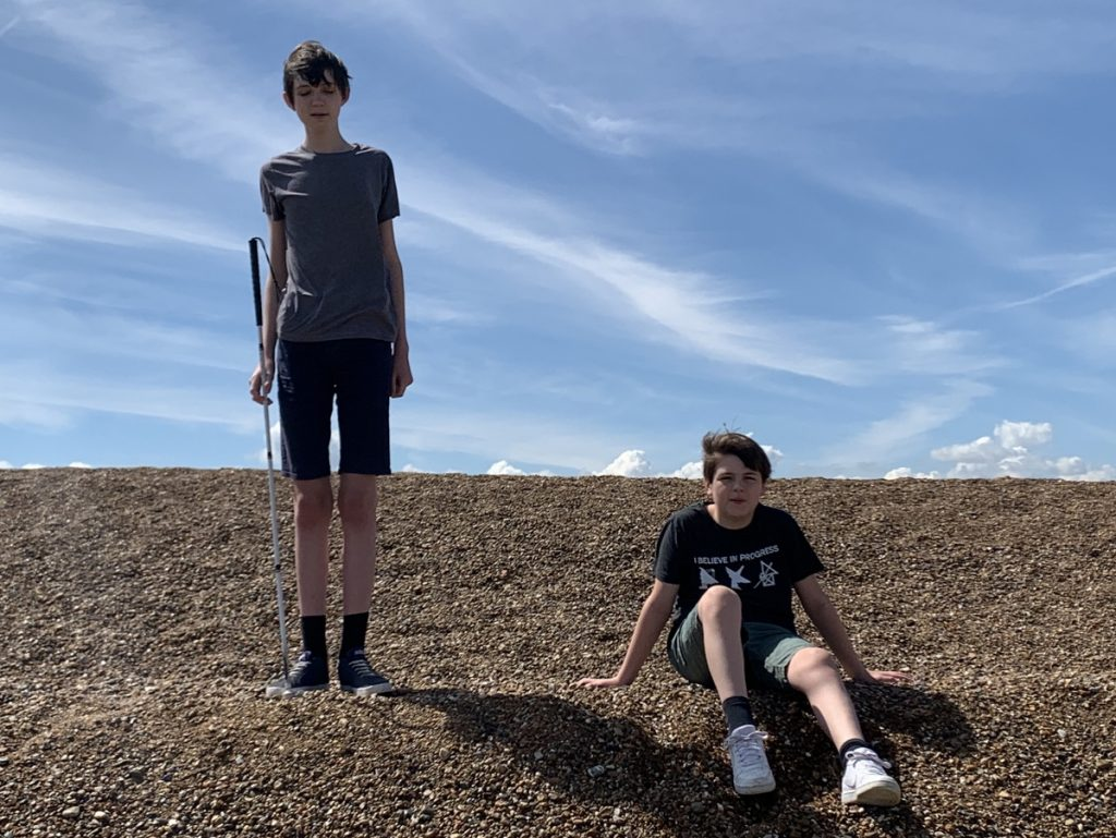 Photo of Ethan (standing) and brother Jasper on a shingle beach.