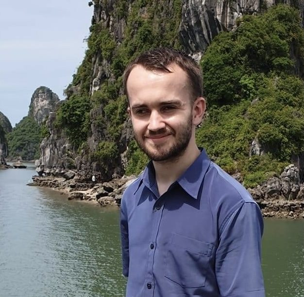 Photo of Liam wearing a blue shirt with a luscious green mountain and river behind him.